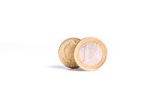 Одна стойка монетки евро перед одной монеткой фунта на задней части белизны Стоковое фото RF