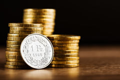 Одна швейцарская откровенная деньг монетки и золота на столе Стоковые Изображения RF