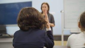 Одноклассники в школе - девушки сидят на таблице и смотрящ во время учителя объясняет урок Стоковое фото RF