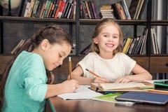 Одноклассники делая домашнюю работу совместно в библиотеке Стоковое фото RF