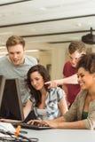 Одноклассники работая совместно в компьютерной комнате Стоковое Изображение