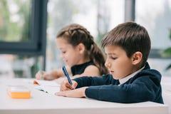 Одноклассники сидя на столе и писать в ученических книгах Стоковые Фото