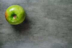 Одно зеленое яблоко на темной каменной предпосылке, взгляд сверху Стоковые Изображения