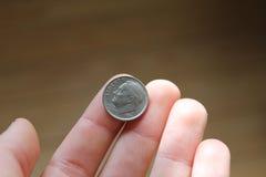 Одно монета в 10 центов в руке стоковые изображения rf