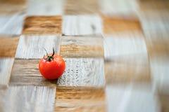 Одно органическое красное tomat на поверхностной доске mosaik с частями различных пород как предпосылка шахматной доски Селективн Стоковые Фото