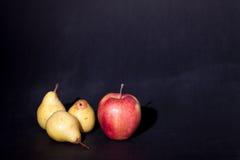 Одно яблоко и 3 груши на черной предпосылке Стоковые Изображения RF