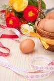 Одно яичко около маленькой корзины с лентами и цветками на деревянных животиках Стоковое Фото