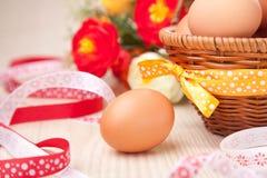 Одно яичко около маленькой корзины с лентами и цветками на деревянных животиках Стоковые Изображения RF