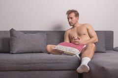 Одно pilow софы кровати молодого человека сидя Стоковое Изображение RF