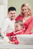 Одн-год-старая девушка в красном платье сидит на кровати в комнате с ее родителями Стоковые Фотографии RF