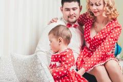 Одн-год-старая девушка в красном платье сидит на кровати в комнате с ее родителями Стоковое Изображение RF