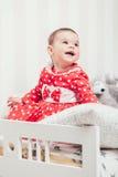 Одн-год-старая девушка в красном платье сидит на кровати в комнате Стоковые Изображения