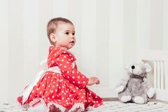 Одн-год-старая девушка в красном платье сидит на кровати в комнате Стоковые Фотографии RF
