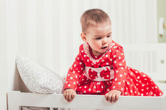 Одн-год-старая девушка в красном платье сидит на кровати в комнате Стоковое Изображение RF