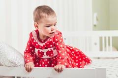 Одн-год-старая девушка в красном платье сидит на кровати в комнате Стоковое фото RF