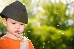 Одуванчик мальчика дуя Стоковая Фотография RF
