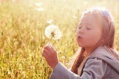 Одуванчик маленькой девочки дуя отсутствующий Стоковое Фото
