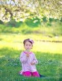 Одуванчик счастливого ребенка дуя outdoors весной Стоковое Изображение