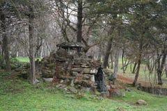 Павильон и пещера в зоне парка среди хвойных деревьев в стоковое фото rf