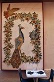Павлин с стеной голубей керамической над таблицей ресторана стоковое фото