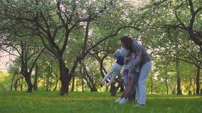 падает семья Мать, отец и 2 дочери бегут и дурят весной парк на зацветая садах видеоматериал