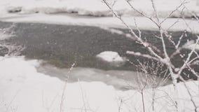 Падает толстый снег на фоне реки горы движение медленное видеоматериал
