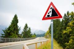 Падать трясет дорожный знак на извилистой дороге в немце Альпах Предупреждающий дорожный знак в горах Стоковое Фото