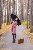 Падение и концепция людей - молодая женщина под зонтиком в парке осени стоковая фотография