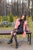 Падение, сезон и концепция людей - молодая женщина сидя на стенде в парке на осени стоковые изображения