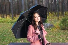 Падение, сезон и концепция людей - молодая женщина сидя на стенде в парке на осени с зонтиком стоковое изображение rf