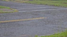 Падения дождевой воды понижаясь в лужицу на асфальте, затопляя потоки дороги должные к проливному дождю в сезоне дождей видеоматериал