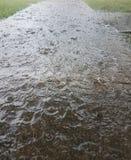 Падения дождя на мостовой и тротуаре стоковая фотография