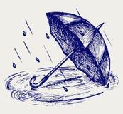 Падения дождя струясь в лужице и зонтике Стоковые Изображения