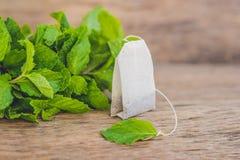 Пакетики чая на деревянной предпосылке с свежей Мелиссой, мятой Чай с концепцией мяты стоковое фото rf