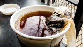 Пакетик чая в бумажной или пластичной кофейной чашке стоковое изображение