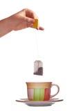 Пакетик чая в руке и чашке изолированных на белой предпосылке Стоковое Фото