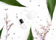 Пакет белой cream бутылки помещенный, пустой ярлыка для насмешки вверх на зеленой предпосылке листвы и цветки Концепция естествен Стоковая Фотография