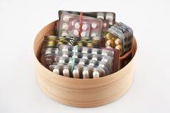 Пакет волдыря с таблетками в круглой деревянной коробке стоковая фотография
