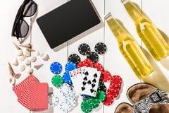 Пакет перфокарт окруженный обломоками покера и разбросанными seashells на белой деревянной предпосылке с космосом экземпляра Стоковое Изображение