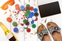 Пакет перфокарт окруженный обломоками покера и разбросанными seashells на белой деревянной предпосылке с космосом экземпляра Стоковые Фотографии RF