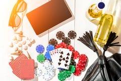Пакет перфокарт окруженный обломоками покера и разбросанными seashells на белой деревянной предпосылке с космосом экземпляра Стоковое Изображение RF