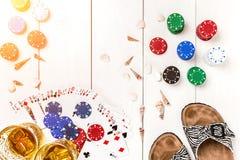 Пакет перфокарт окруженный обломоками покера и разбросанными seashells на белой деревянной предпосылке с космосом экземпляра Стоковые Изображения