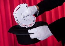 Пакет перфокарт руки волшебника дуют удерживанием, котор Стоковая Фотография