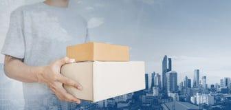 Пакет удерживания человека кладет пакет в коробку, с предпосылкой города Бангкока Стоковое Фото