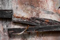 Пакостная бетонная стена с досками распадаться и ржавыми кусками металла стоковое изображение