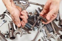 Пакостная рука работника с инструментами для ремонтировать машины в мастерской Стоковые Изображения