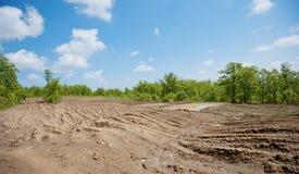 Пакостная сломанная сельская дорога с глубокими следами автошины стоковое фото