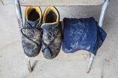 Пакостные ботинки и футболка с следом ноги пыли работника на лестнице лестницы Стоковое фото RF