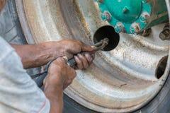 Пакостные руки механика используя механическое оборудование для заполнять большой Стоковые Фото