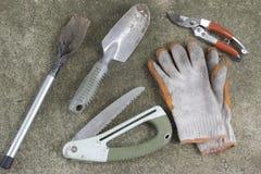Пакостные садовничая инструменты, лопаткоулавливатель, перчатки, подрезая ножницы и пила стоковое фото rf